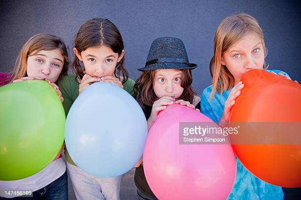 four girls blowing up large balloons