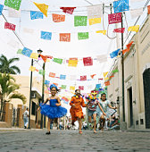Four girls (5-9) running in street at fiesta