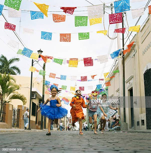 Four girls (5-9) running in street at fiesta