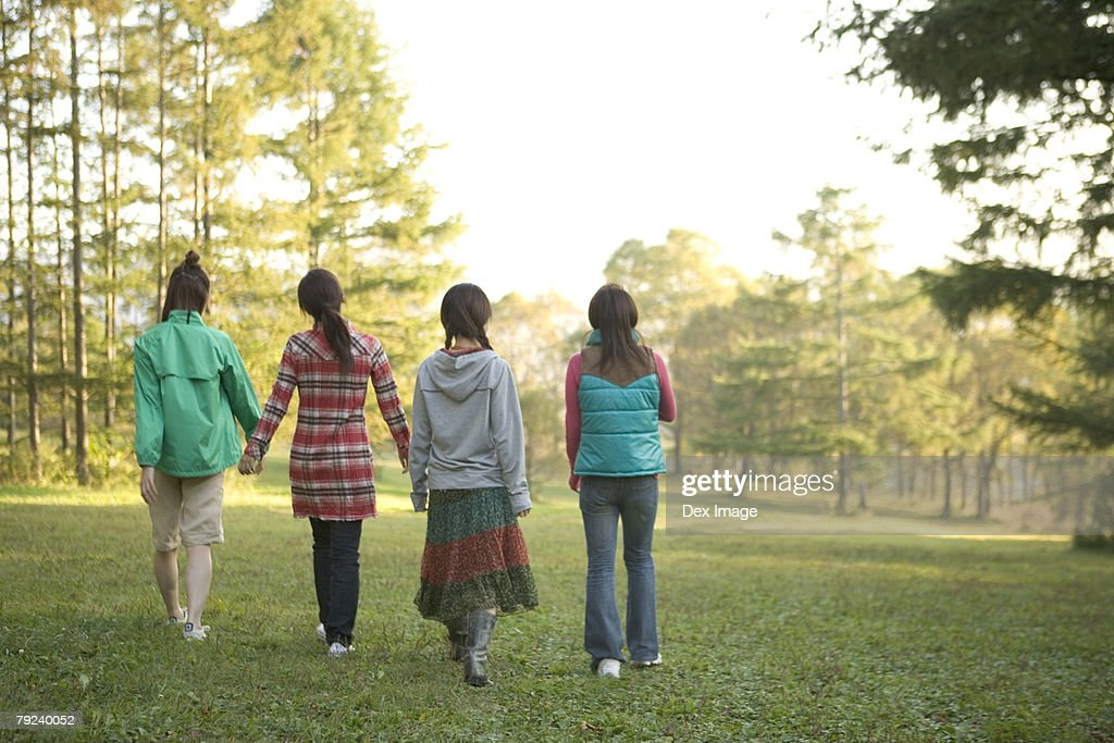 Four girls strolling in the park, back view : Stock Photo