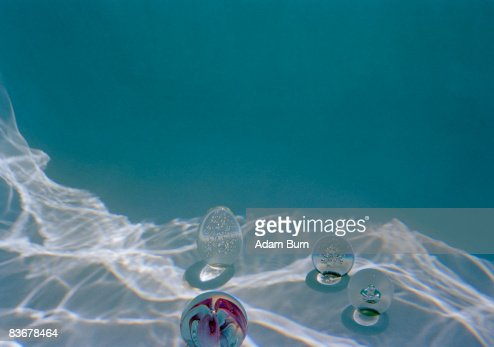 Four glass paperweights sitting at the bottom of a swimming pool