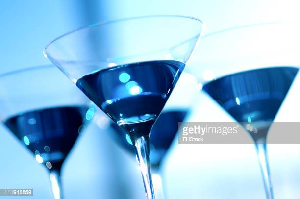 Four Glittering Blue Martinis Glasses on Surreal Background