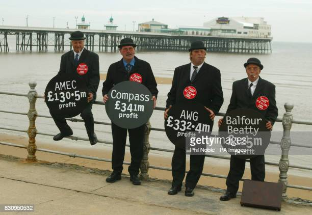 Four GMB protesters dressed as 'Fat Cat' business men pose with 'wrecking balls' displaying the names of firms involved in contracts funded by the...