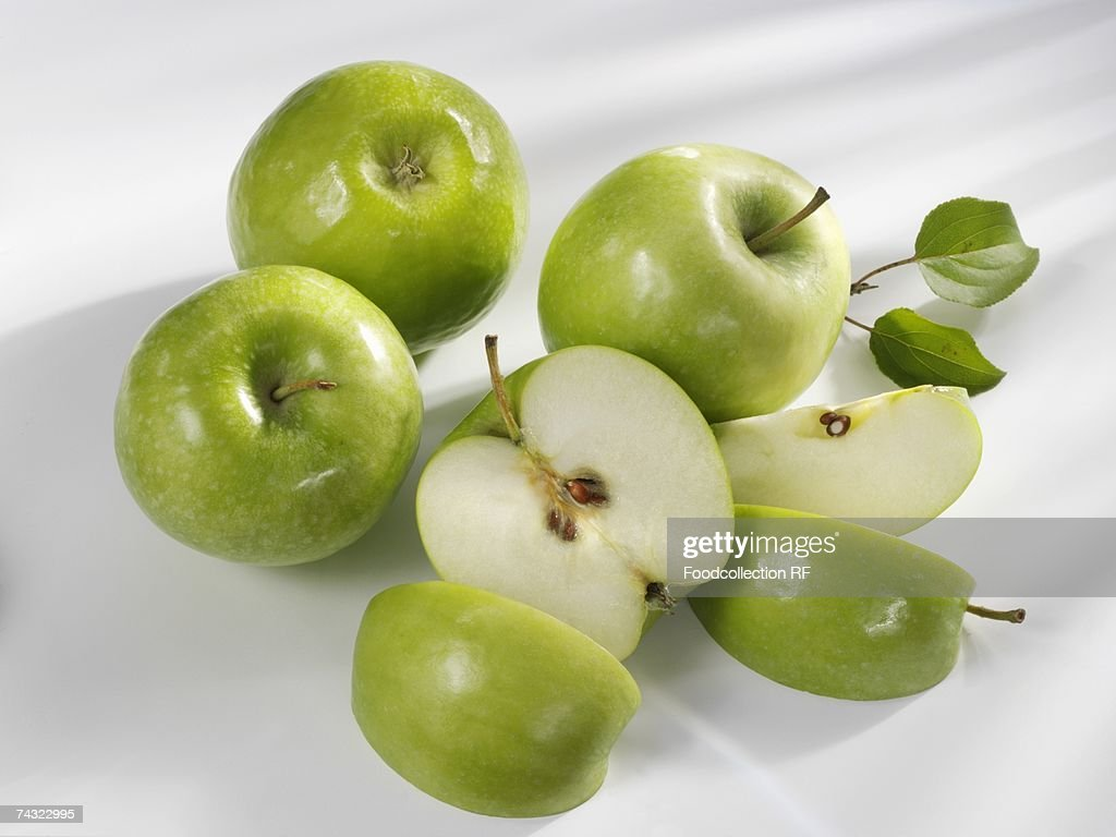 Four 'Granny Smith' apples, one cut into pieces : Stock Photo