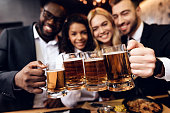 Four guys and girls ordered a beer in the bar. A group of young people is resting in a bar. They drink alcoholic beverages and have fun. They are fun to be together.