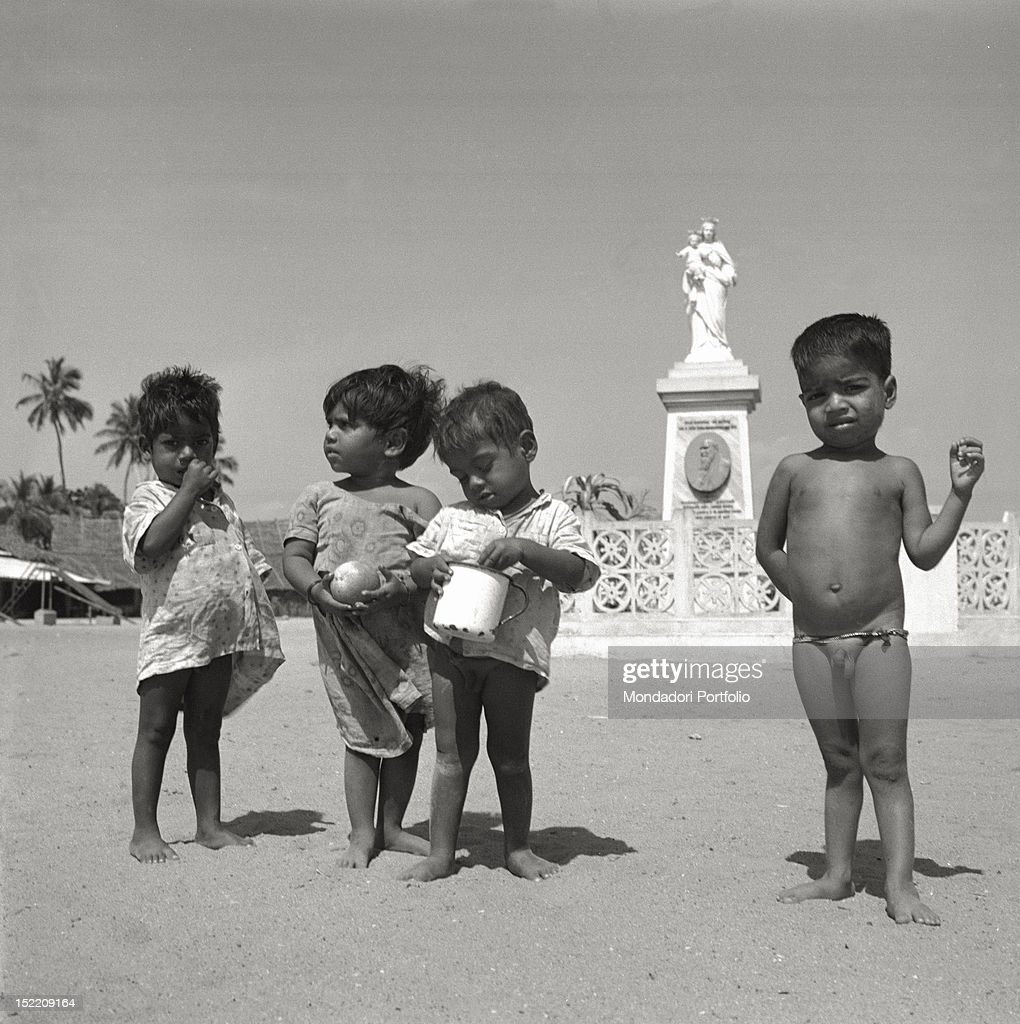 child naked  Four half-naked children in front of the statue of Madonna with Child, in