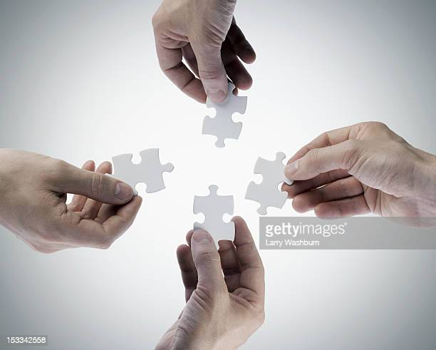 Four hands holding jigsaw puzzle pieces, directly above