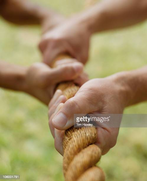 Four hands pulling on thick rope