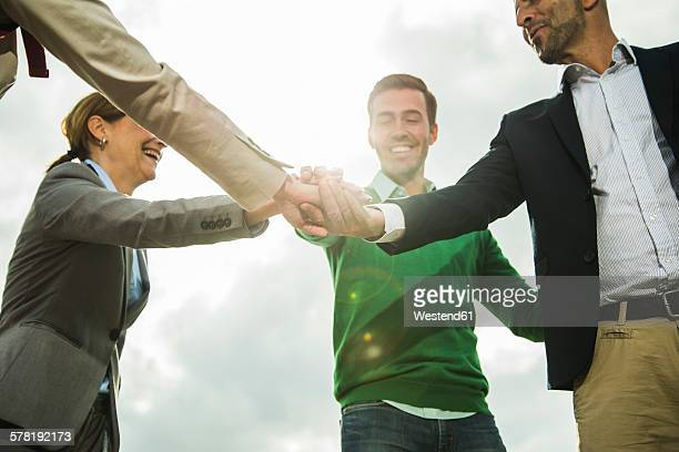 Four happy businesspeople stacking their hands outdoors