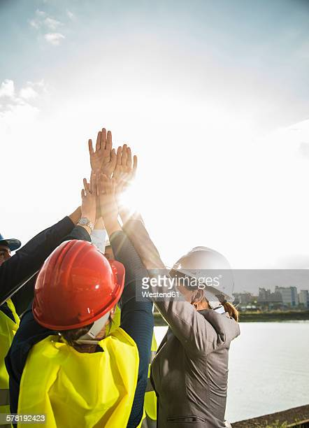 Four happy businesspeople with safety helmets raising their hands together