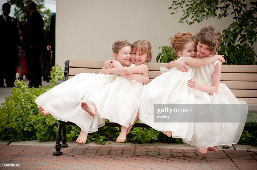 Four Happy Flower Girls Hugging Each Other in Formal Dresses