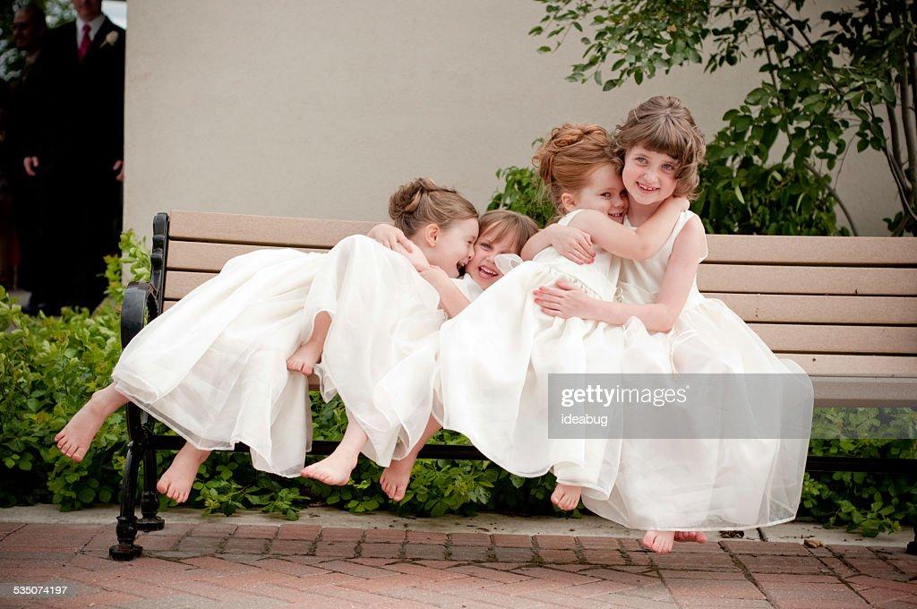 Four Happy Flower Girls Sitting on Bench in Formal Dresses