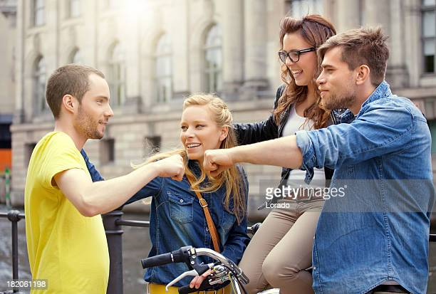 four happy friends meeting in city