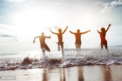 Four happy friends runs to sunset beach : Foto stock