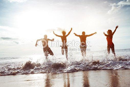 幸せな 4 人の友人は、サンセットビーチ : ストックフォト