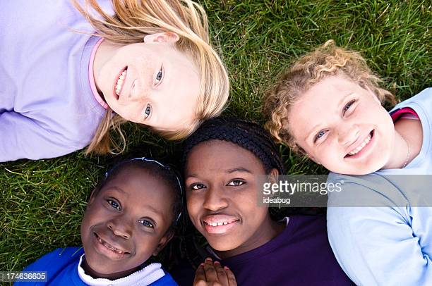 Four Happy Girls Lying in the Grass