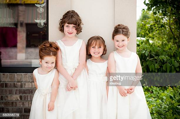 Four Happy Little Flower Girls Standing Together in Formal Dresses