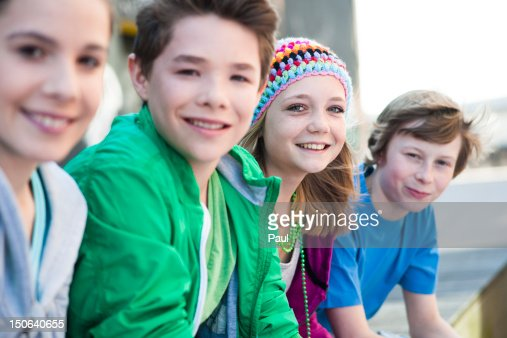 Four happy teenagers sitting in row : Stock Photo