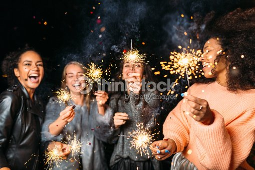 Four happy women holding sparklers, throwing confetti : Stock Photo