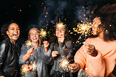 Four happy women holding sparklers, throwing confetti