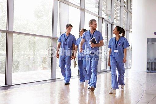 Four healthcare workers in scrubs walking in corridor : Stock Photo