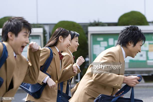 Four high school students smiling and running, side view, Japan