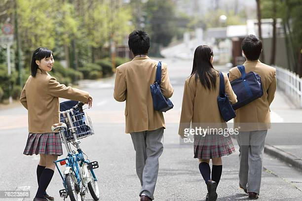 Four high school students walking down the street together, side by side, portrait for a girl, rear view, Japan