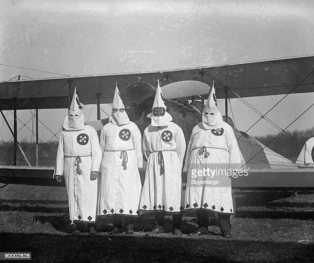 Four Hooded White Sheeted Ku Klux Klan Member pose in Robes Hoods in front of Airplane