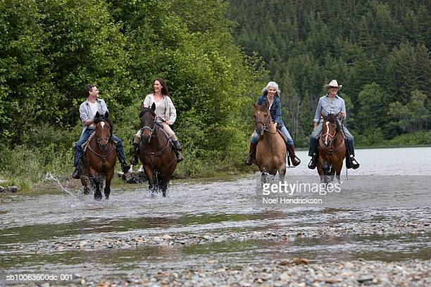 Four horse riders crossing river