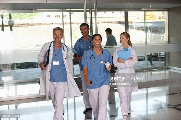Four hospital workers walking in corridor holding clipboards and smiling
