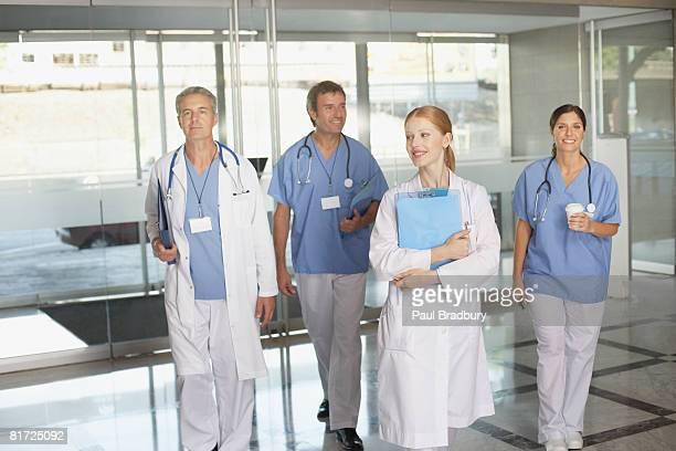 Vier hospital Arbeitnehmer zu Fuß in Gang halten clipboards und