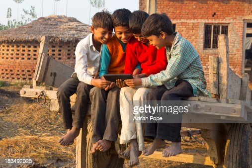 Four Indian boys looking at tablet device