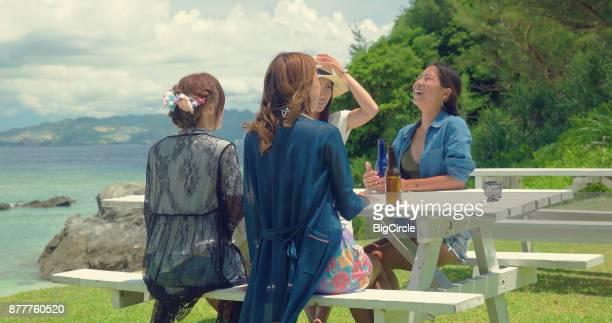 Four Japanese female having fun by the beach.