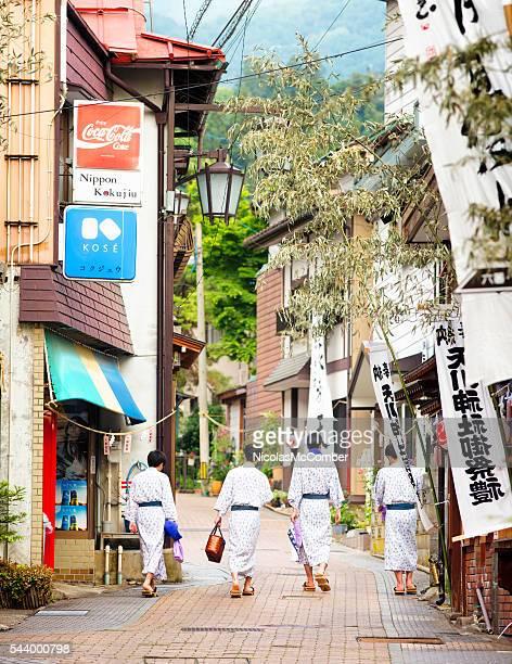 Four Japanese men wearing yukatas walking in Shibu-Onsen street