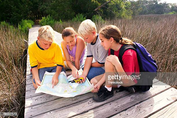 Four kids kneel and sit on a boardwalk looking at a map while taking a day hike