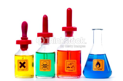 Four labelled bottles of coloured chemicals. : Stock Photo