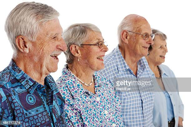 Four laughing seniors in three-quarter profile on white