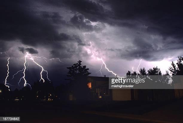 Four lightning strikes over houses and trees in Denver