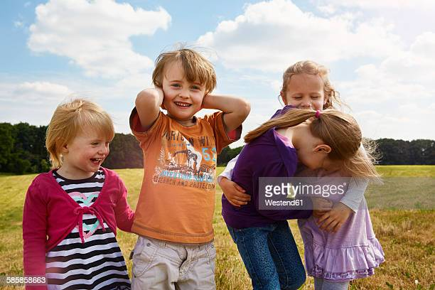 Four little children playing on a meadow