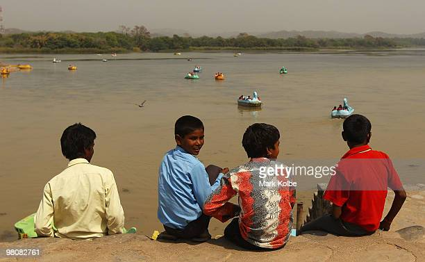Four local boys watch as vistors hire boats and crusie around Sukhana Lake on March 26 2010 in Chandigarh India