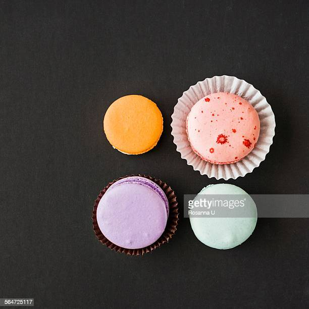 Four macarons against black background, overhead view