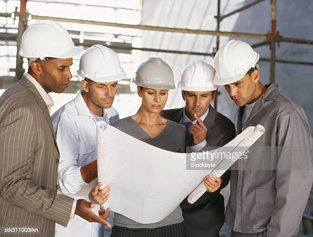 four male architects and a female architect discussing a blueprint