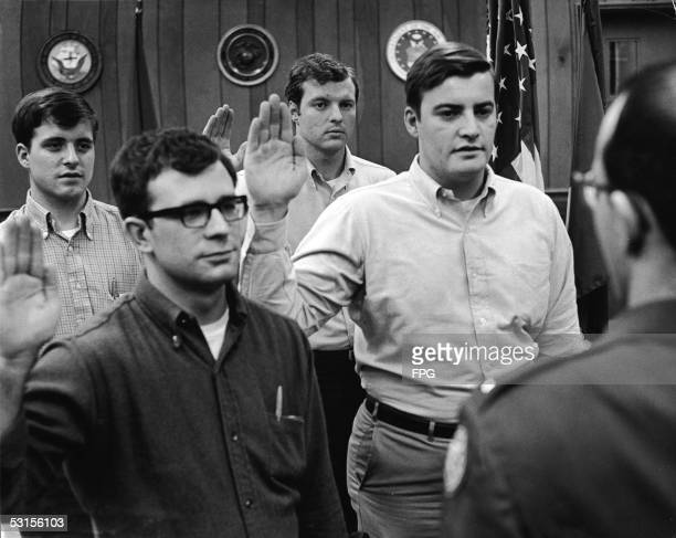 Four male civilians with their hands raised to take an oath stand before a military personnel man and prepare to be sworn in and become recruits in...