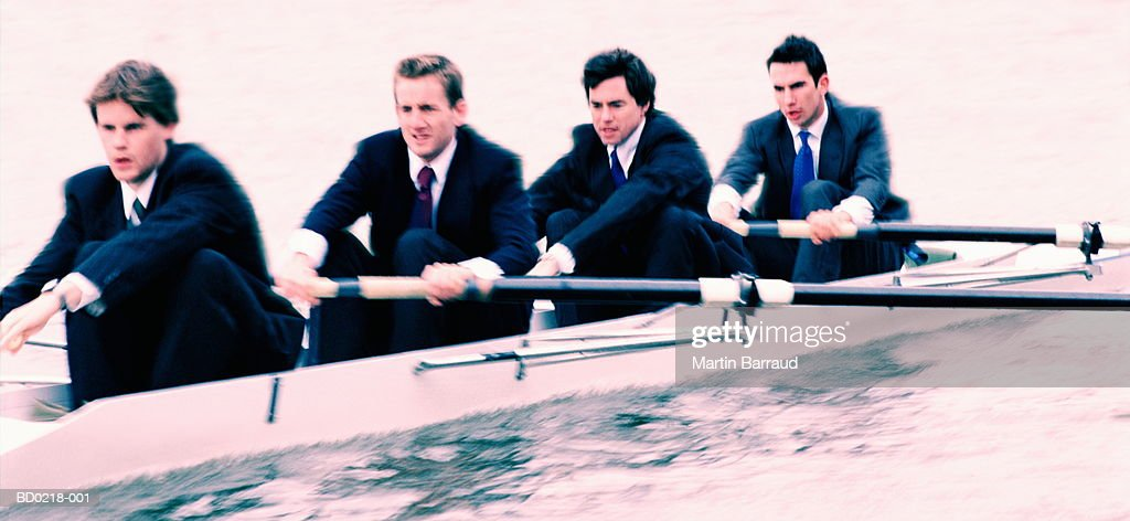 Four male executives in rowing boat (Digital Enhancement) : Stock Photo