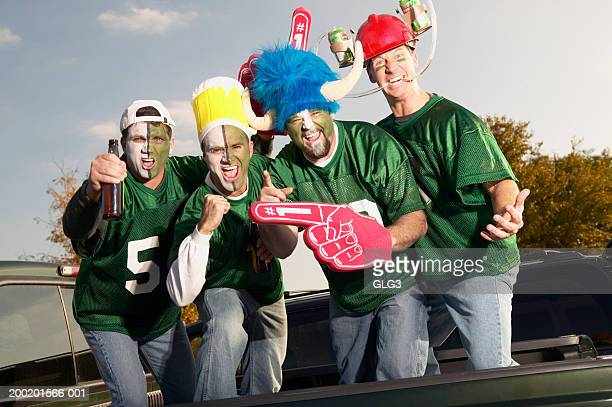 Four male football fans wearing face paint, gesticulating