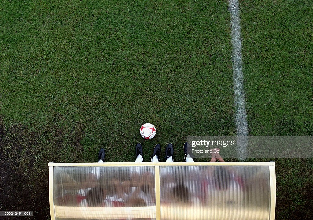 Four male football players sitting on bench, overhead view