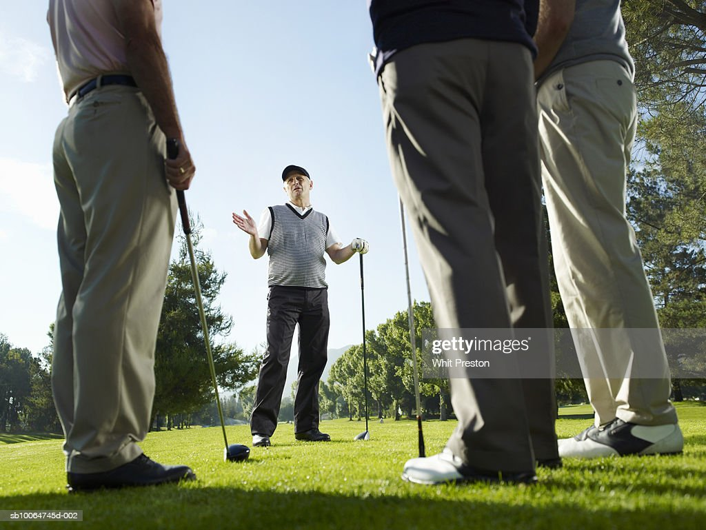 Four male golfers talking, leaning on clubs, surface level : Stock Photo
