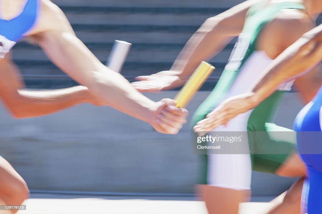 Four male runners passing relay baton : Stock Photo