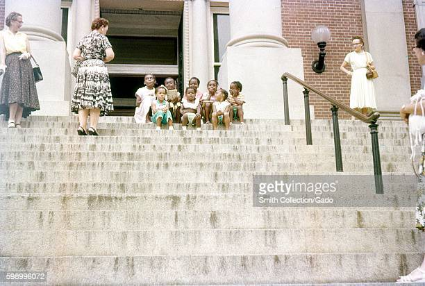 Four mature Caucasian women wearing dresses and heels stand at various positions on the marble stairs of the Maryland State House and look with...