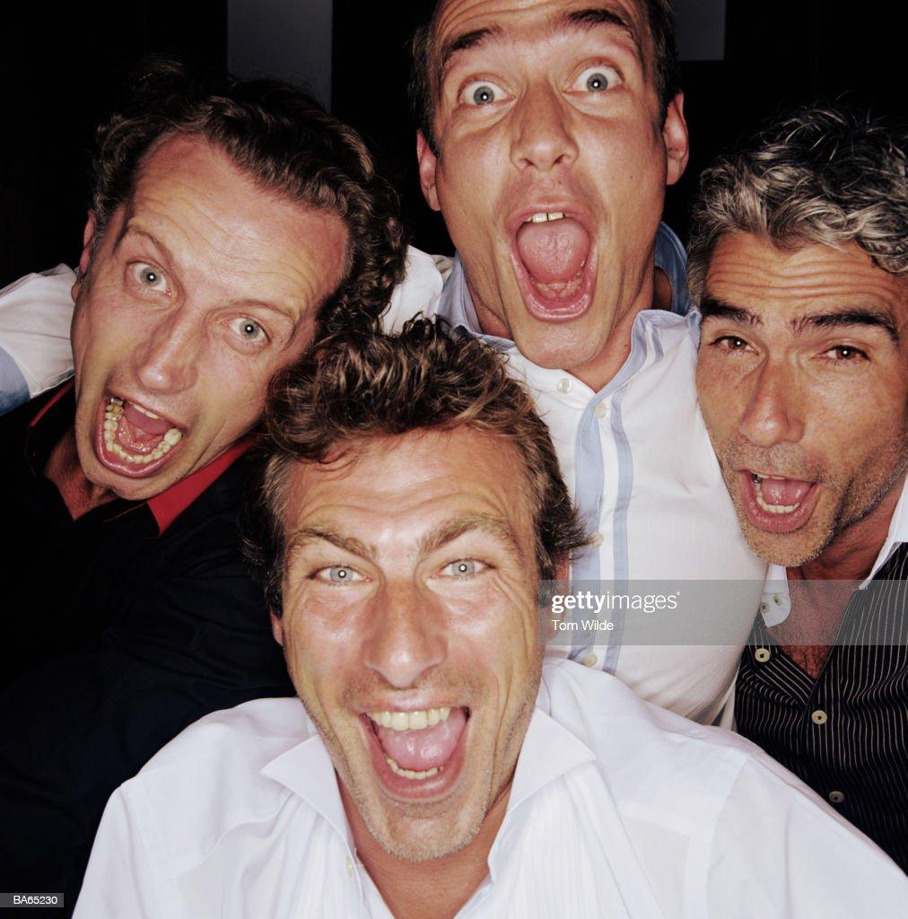 Four mature men cheering, close-up, portrait